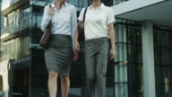 MS CU of businesswomen walking outdoors, businessman using mobile phone, selective focus