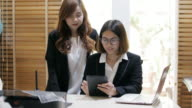 Businesswomen working together at laptop and tablet in office