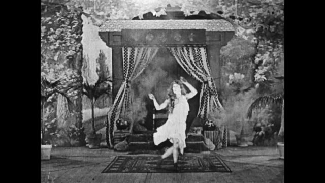 Buster Keaton, in drag, dances with binoculars and flips around the stage for a large cheering audience, one audience member jeers