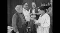 Buster Keaton is confused by sudden generous outpouring of money from roomful of gruff men