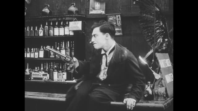 Buster Keaton kicks the dead bartender under the floorboards