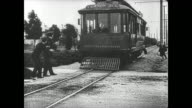 Buster Keaton poses like a statue to elude the police after he fails to escape from them on a trolley