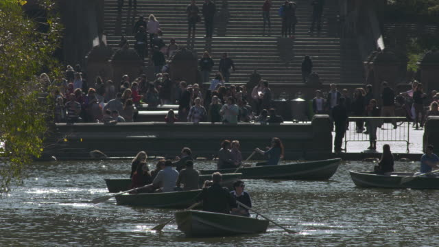 Busy Central Park day with visitors enjoying boats and Bethesda Fountain during Autumn.