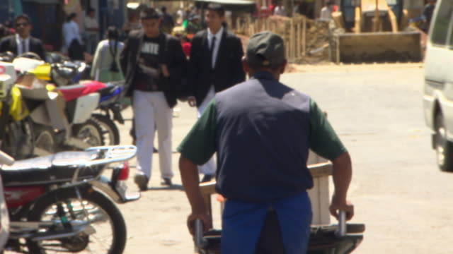 Busy comings & goings on street, roadworks, man with wheelbarrow, Cochabamba, Bolivia