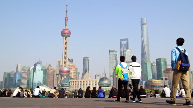 Busy crowds overlooking The Bund and Huangpu River - Shanghai, China