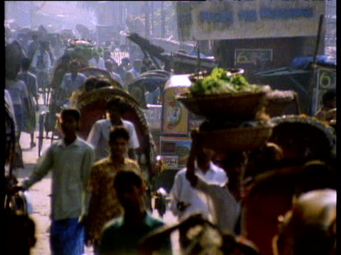 Busy Dhaka street scene with rickshaws bicycles and pedestrians