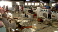 PAN Busy indoor fish market with customers perusing the variety of fish displayed in large freestanding bins and trays / Manama Bahrain