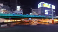 MS T/L Busy intersection and train overpass in Shinjuku business and entertainment district / Tokyo, Japan
