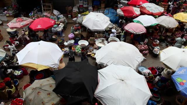 A busy market in Accra, Ghana where umbrellas protect vendors 2