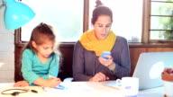 Vielbeschäftigte Mutter im home-Office Schreibtisch mit Töchterchen