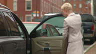 MS Busy mother and daughter (6-7) getting into car and talking on cell phone, Richmond, Virginia, USA