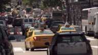 Busy New York City traffic moves away from camera on one way street