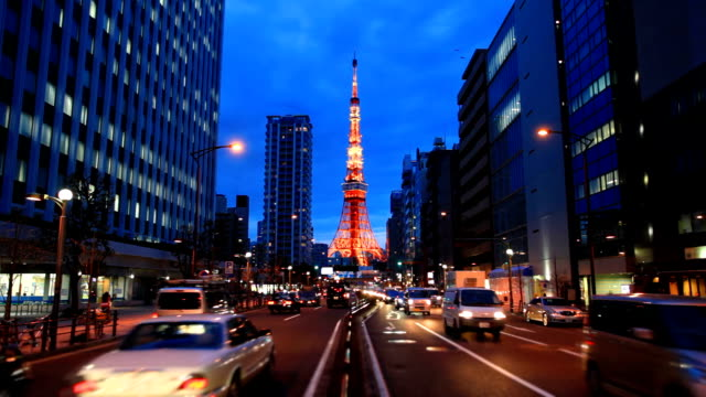 Busy street at night with Tokyo Tower.