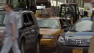 A busy street scene with cars stopped at a light and construction on the 2nd avenue subway line goes on behind.