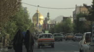 WS Busy street with golden domed mosque in background / Teheran, Iran