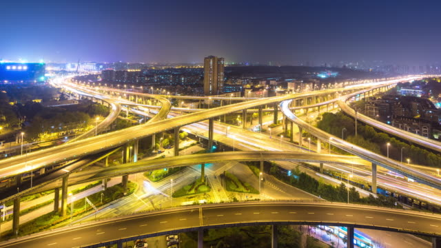 drukke verkeer op de kruising van de weg met skyline en skyline van hangzhou binjiang district bij nacht timelapse 4k