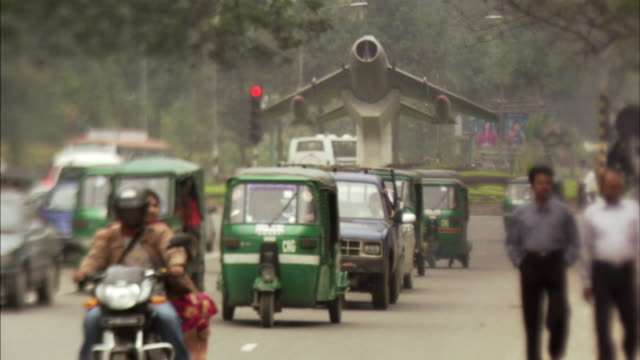 MS, SELECTIVE FOCUS, Busy traffic on street, airplane monument in background , Dhaka, Bangladesh