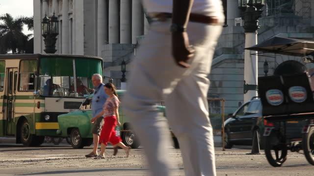 MS, busy traffic w/ vintage American cars & pedestrians in Cuba