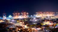 Geschäftige Kran Laden von Containern im Hafen bei Nacht, Zeitraffer.