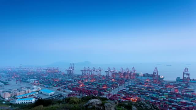 Geschäftige Kran Laden von Containern im Hafen, beleuchtete Zeit lapse.dusk zur Nacht.
