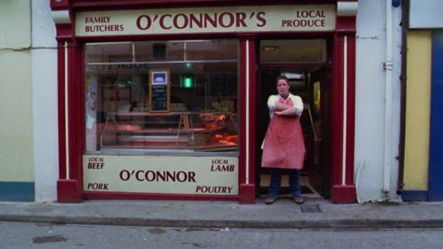 PORTRAIT butcher crosses his arms standing in doorway of 'O'Connor's' butcher shop / Dublin, Ireland