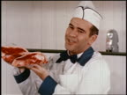 1950 butcher holding up steaks + talking to someone off-screen
