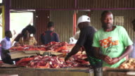 MS Butcher packaging meats for people in semi enclosed building / Windhoek, Khomas, Namibia