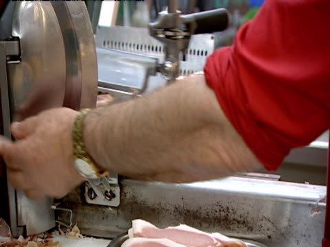 A butcher uses meat slicer to make bacon rashers