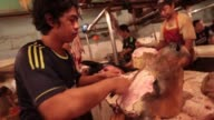 Butchers prepare cow heads at a stall at the Santa market in Jakarta sharpening knifes and removing skin Butcher's stall at the Santa market in...