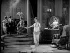 1926 B/W WS Butler removing robe from man (Ben Turpin) who stretches and dances around room while women play musical instruments / USA