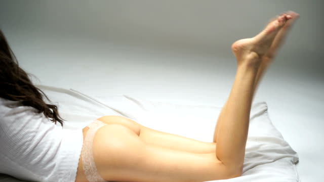 Buttocks and legs of slim woman lying on bed