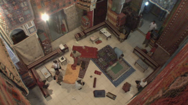 WS HA Buyers looking at rugs in large rug emporium, Fez, Morocco
