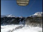Cable car moves high over snowy ground towards snow capped mountain and trees against blue sky Val D'iserre