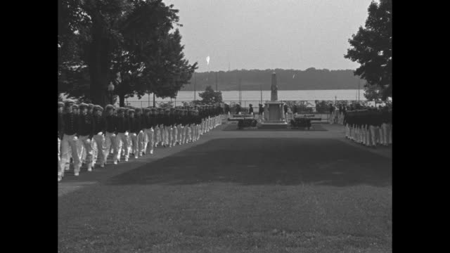 Cadets from the United States Naval Academy march in formation on campus during World War II / cadets march into church / CU anchor