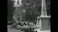Cadets from the Unites States Naval Academy march in formation on campus during World War II / dome of a church / American flag flying