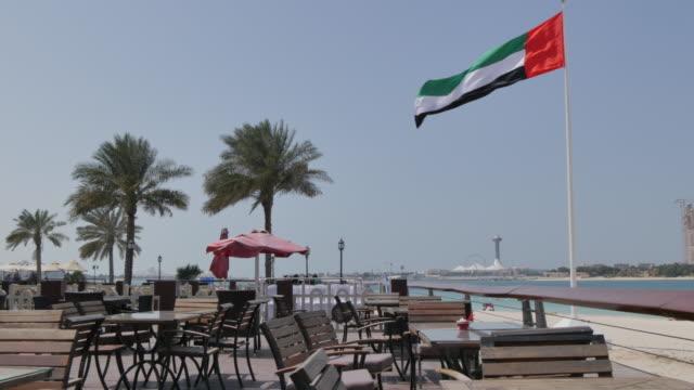 Cafe and UAE flag on the Corniche Road, Abu Dhabi, United Arab Emirates, Middle East, Asia