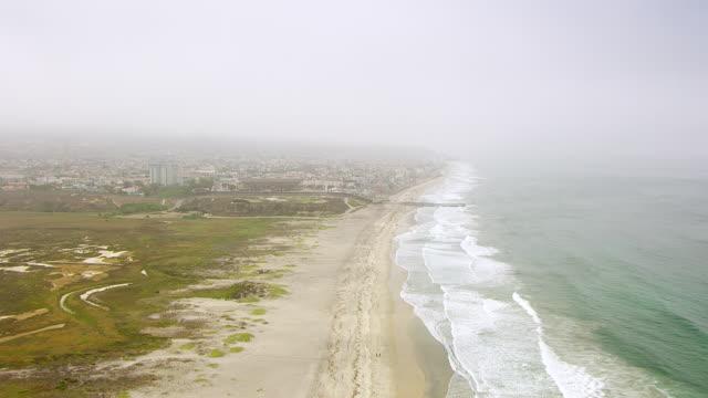 WS AERIAL POV California coastline foreground approaching international border with Tijuana Mexico in hazy background / San Diego, California, United States