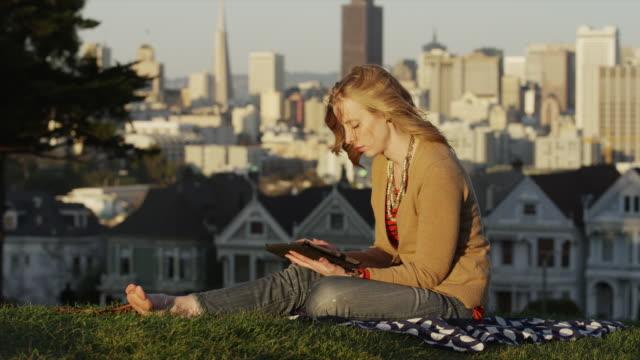 USA, California, San Francisco, Alamo Square Park, Woman sitting on grass and using digital tablet