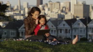 USA, California, San Francisco, Alamo Square Park, Woman with daughter (4-5) sitting in park and using digital tablet