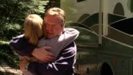 CU, USA, California, Shaver Lake, Couple looking at motor home, hugging