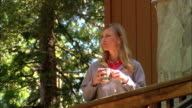 CU, LA, USA, California, Shaver Lake, Woman drinking coffee at bungalow porch