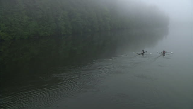 HA WS Calm Connecticut River at dawn with two people rowing past in single sculls/ Hanover, New Hampshire, USA