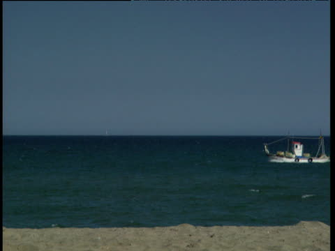 Calm sea fishing boat passes right to left beach in foreground Torremolinos