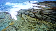Calm waves splash on rocky shore