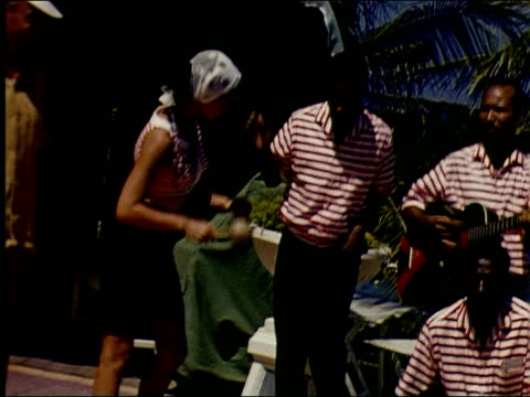 Calypso band in red striped shirts play at Tower Isle Hotel while tourists in straw hats play maracas and bongo drums and dance with them shot is...
