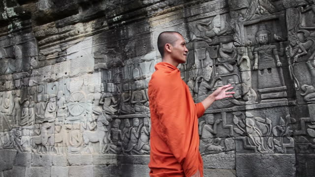Cambodian monks discuss bas-reliefs at the Bayon Angkor