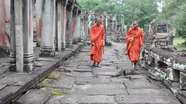 Cambodian monks walking at Bayon exterior