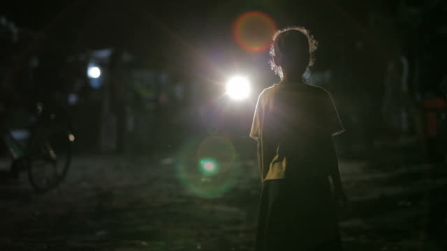 Cambodian street child in moving traffic, homeless girl