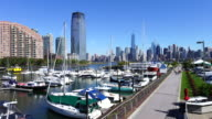 Camera captures anchored ships and hi-rise residential buildings at Liberty Harbor Marina. Manhattan skyscrapers can be seen at opposite shore of Hudson River from Liberty State Park