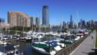 PAN Camera captures anchored ships and hi-rise residential buildings at Liberty Harbor Marina. Manhattan skyscrapers can be seen at opposite shore of Hudson River from Liberty State Park